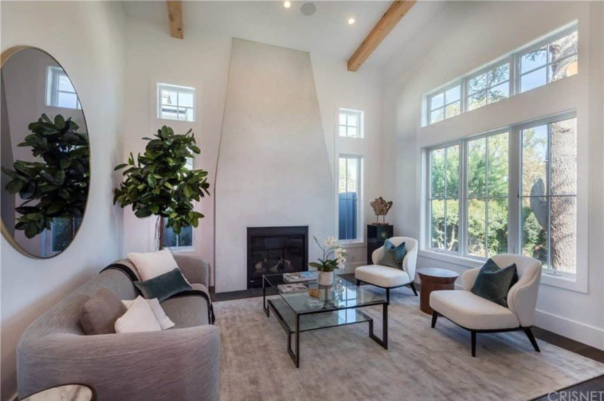 A formal living room with a super comfy gray couch and a glass top center table set on the rug covering the hardwood flooring. The area also has a tall ceiling with beams and a fireplace.