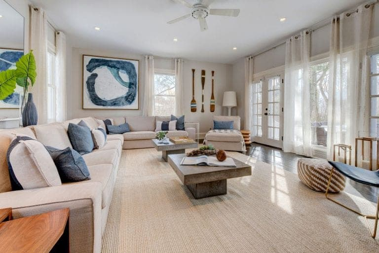 A spacious living room boasting a large area rug covering the hardwood flooring. The room offers a large L-shaped sofa set and a pair of rustic center tables.
