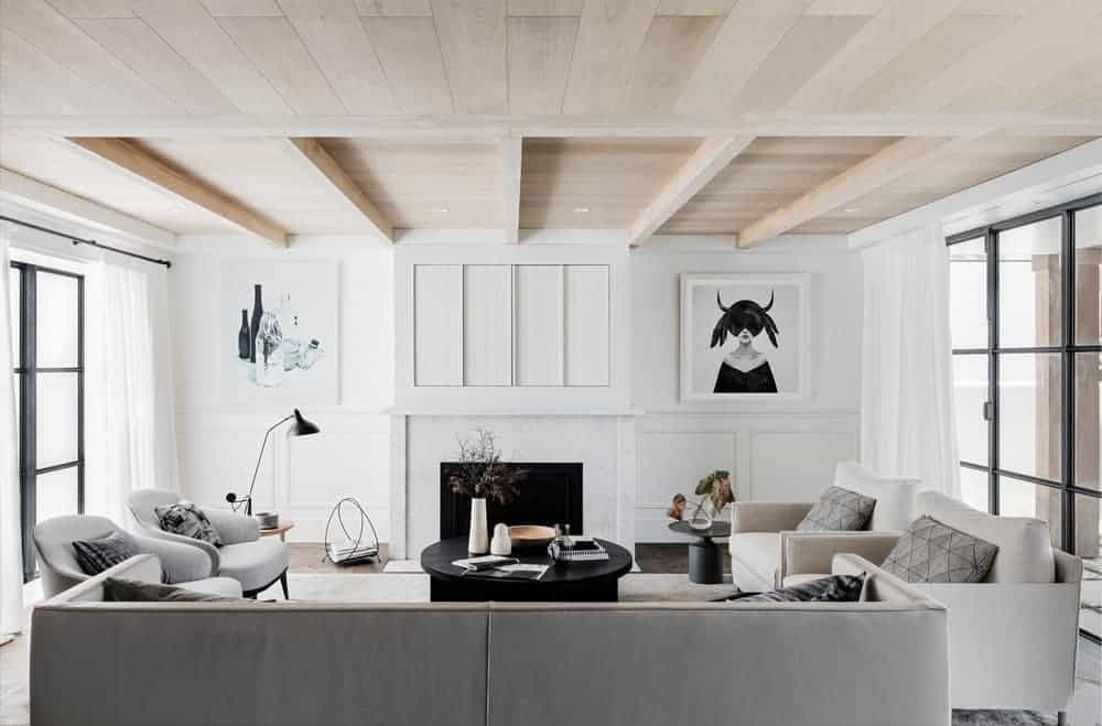 This living room boasts a set of modern seats and a fireplace, along with artistic wall decors. The room also features white walls and a wooden ceiling with beams.