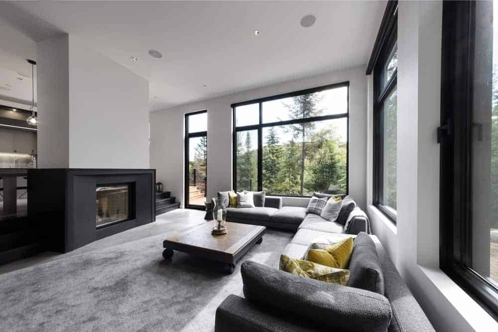 Modern living room with glass windows and a large area rug. The room has a large L-shape sofa set and a stylish center table, along with a fireplace.