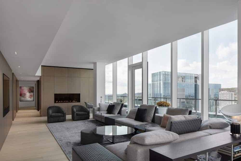 Large modern living space featuring a large gray sofa set with a black accent and a large gray rug. The area is surrounded by tall glass windows and walls. There's also a gas fireplace on the side of the room.