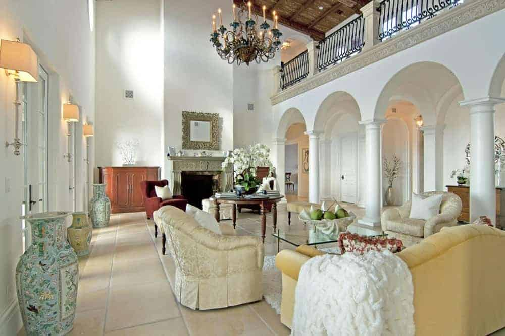 Large living room featuring tiles flooring and a two-storey wooden ceiling with a gorgeous chandelier hanging from it. The room has an elegant set of seats along with a fireplace.