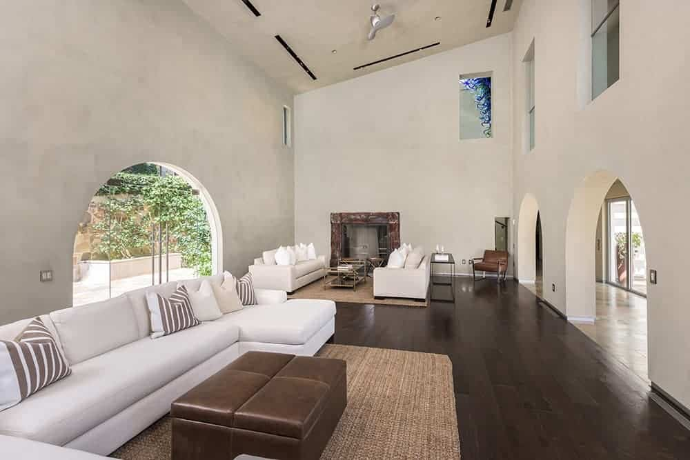 Large Mediterranean living room with hardwood floors and a tall ceiling, along with a set of white seats and a fireplace.