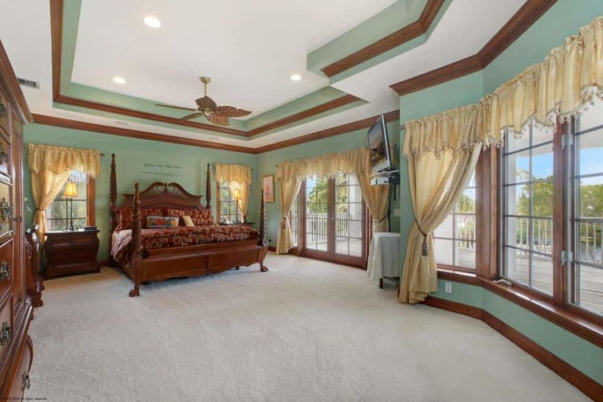 Large primary bedroom featuring a stunning tray ceiling and carpeted flooring. The large classy bed is surrounded by the room's green walls and large windows with gold-colored window curtains.