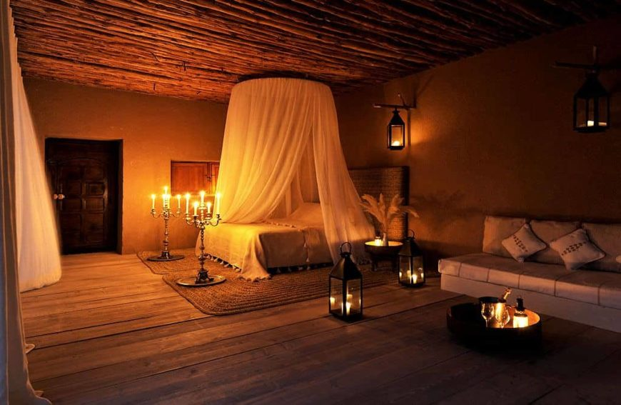 A gloomy Mediterranean style primary bedroom with a wooden ceiling and hardwood flooring. The bed setup is perfect for an intimate night.