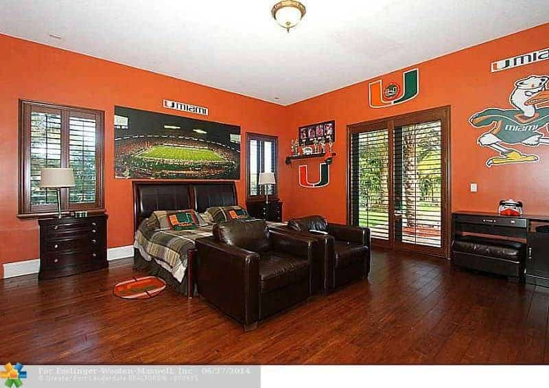 This primary bedroom features orange walls and hardwood floors. The room has a classy bed set together with dark brown leather seats.