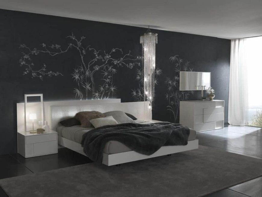 Contemporary primary bedroom boasting a decorated black wall along with a white bed set with white bedside tables. The dark tiles flooring is topped by a gray area rug.