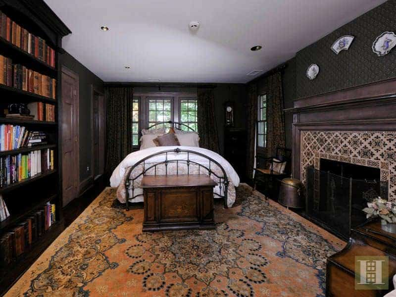 A primary bedroom with elegant black walls. It features a large bookshelf along with a large decorated fireplace. The dark hardwood flooring is topped by a large stylish area rug.