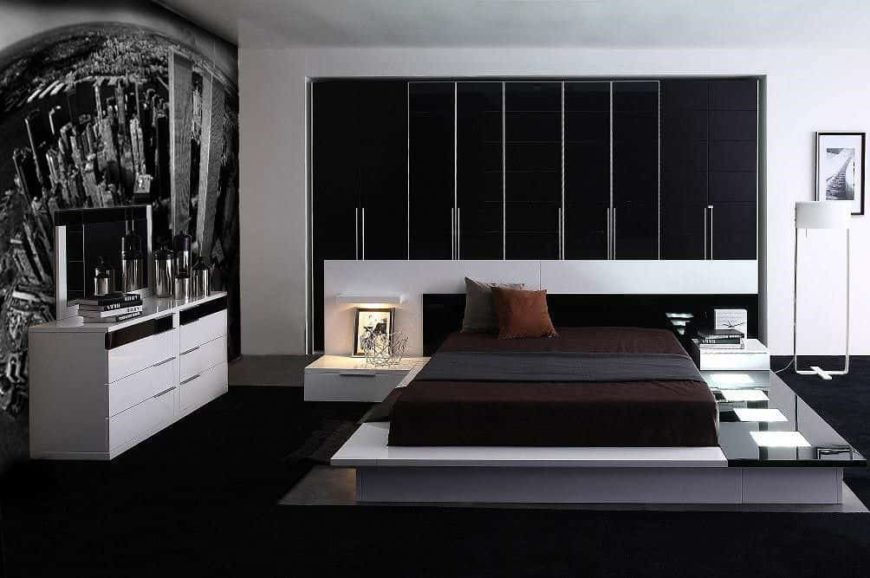 Contemporary primary bedroom with a black and white color scheme. It has a stylish bed setup with built-in bedside tables. The wall features an eye-catching design.
