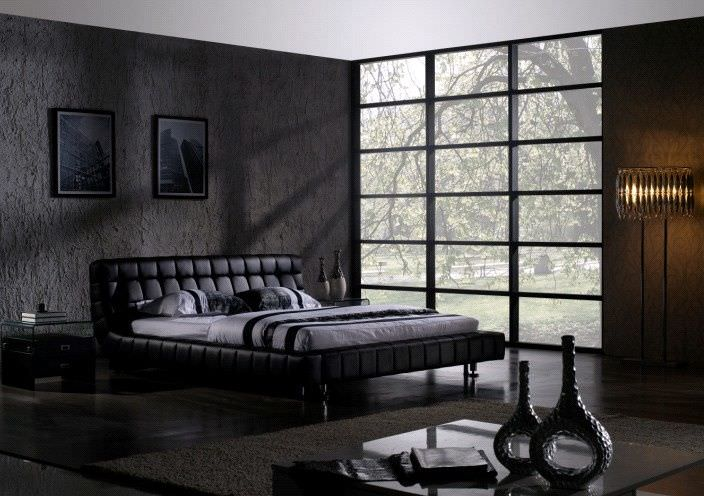 Modern primary bedroom with a stylish black wall and dark-finished flooring. The large black and gray bed set looks absolutely stunning.