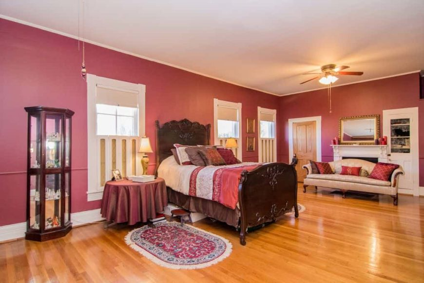 Large primary bedroom featuring red walls and hardwood floors, together with the white regular ceiling. The room has a gorgeous bed setup and a nice couch on the side near the fireplace.
