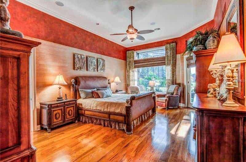 Large primary bedroom with elegant red walls and hardwood floors. The room boasts a classy bed set lighted by table lamps on both sides.