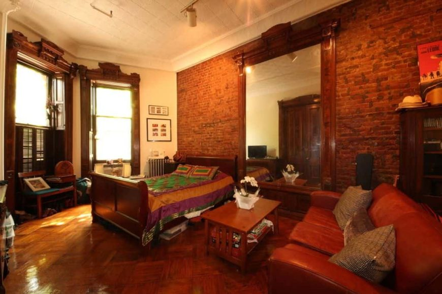 Large primary bedroom boasting a tall ceiling, a brick wall and stylish hardwood flooring. The room has a nice double-sized bed and a brown leather couch on the side.