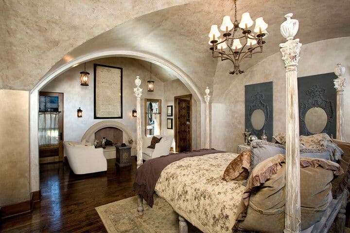 Primary bedroom boasting a groin vault ceiling and hardwood flooring. The room boasts a classy bed set lighted by a gorgeous chandelier, along with a sitting area next to the fireplace.