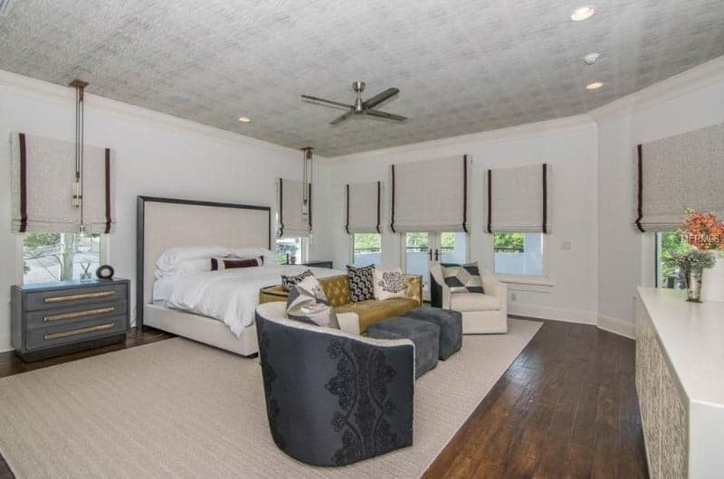 Large primary bedroom with white walls and hardwood flooring. The room offers a nice cozy bed along with a small living space set on the area rug.