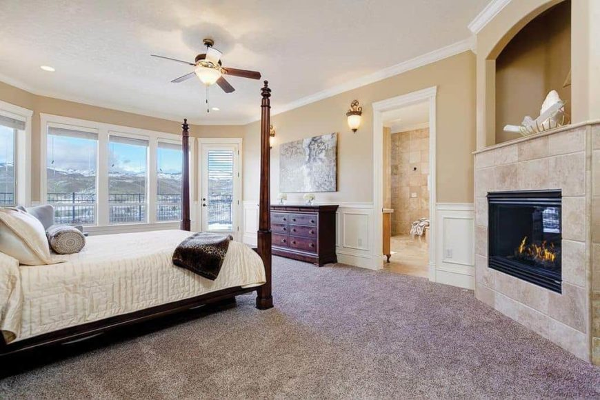 This primary bedroom offers a classy bed along with a corner fireplace. The room also offers its own large bathroom.
