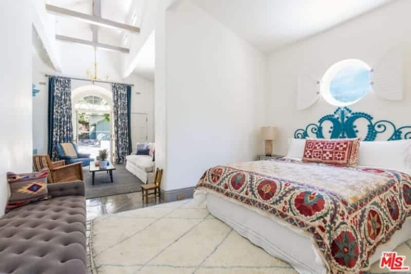 Large primary bedroom featuring a large bed set along with a personal living space.