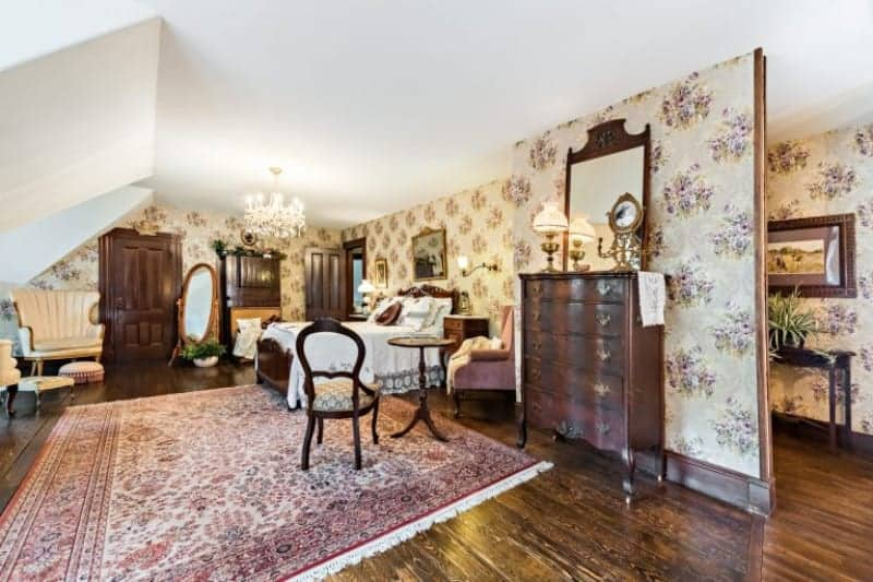 Large primary bedroom boasting elegantly designed walls and hardwood flooring topped by a classy area rug. The room offers a gorgeous bed set lighted by a beautiful chandelier and wall lights.