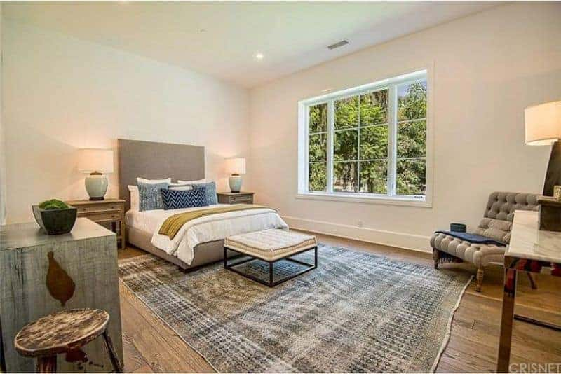 This primary bedroom boasts a large modish bed set lighted by table lamps on both sides. The room has hardwood flooring topped by a stylish gray area rug.