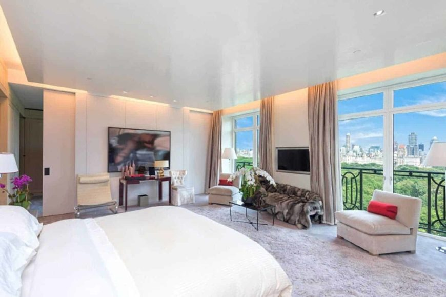 Large primary bedroom with a stunning ceiling design and gray carpet flooring topped by a large area rug. The room offers a large white bed and a large flat-screen TV on the wall.