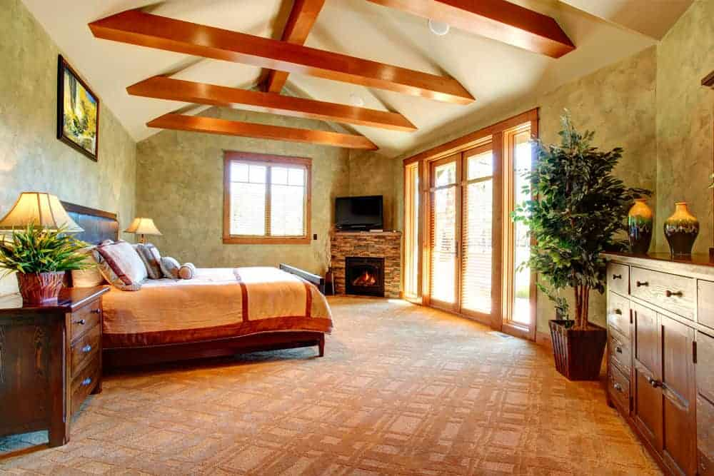 Large primary bedroom with brown carpet flooring, green walls and a tall ceiling with exposed beams. The room offers a large bed set and a fireplace in the corner together with a TV on top of it.