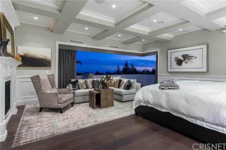 Large primary bedroom featuring a coffered ceiling and hardwood flooring, along with a large bed, a personal living space and a fireplace.