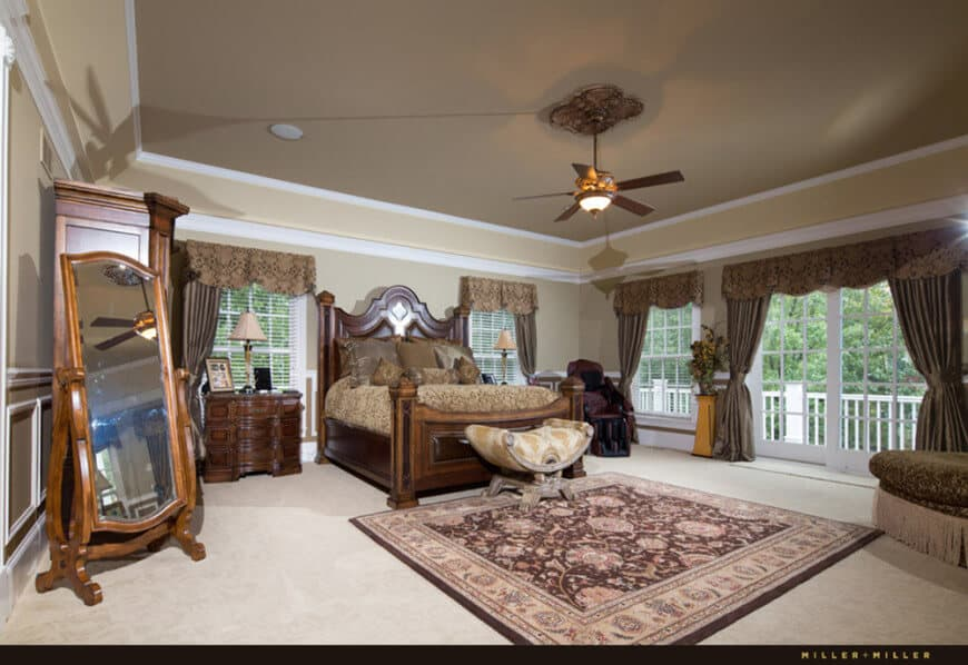 Large primary bedroom featuring a gorgeous tray ceiling, carpeted flooring and windows with beautiful brown window curtains. The room offers a large elegant bed set.