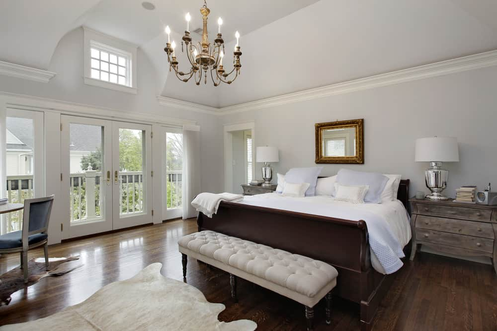 Large primary bedroom featuring light gray walls and a tall ceiling, along with hardwood flooring. The room has two rustic bedside tables and a rustic dining nook, lighted by a glamorous chandelier.