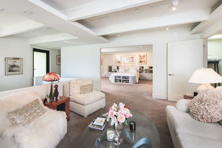 Huge primary suite boasting a large bedroom space and a large personal living space, surrounded by white walls and ceiling along with carpet flooring.