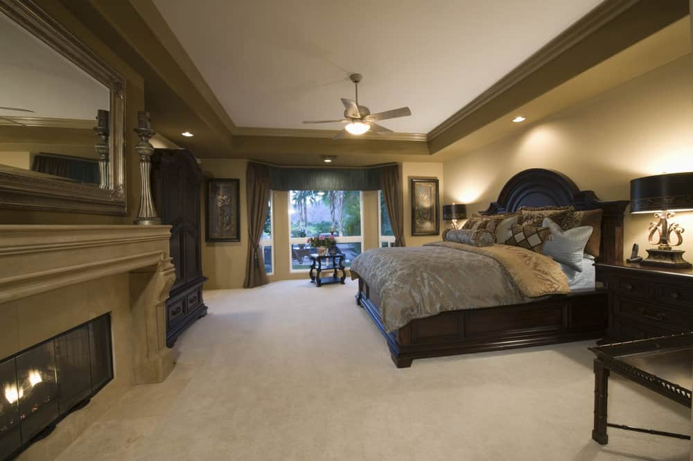 Spacious primary bedroom boasting a stunning tray ceiling with brown walls and carpeted flooring. The room has a large bed along with a large fireplace.