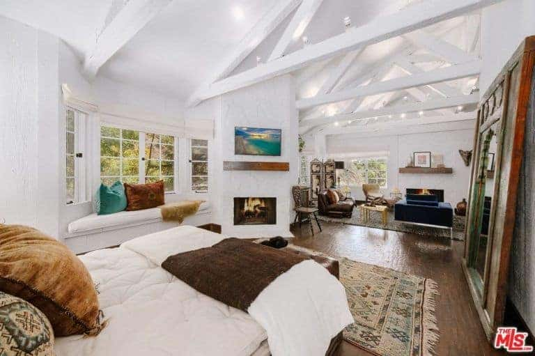 Large primary bedroom with a private bed space and its own living space surrounded by white walls and a white ceiling with exposed beams.