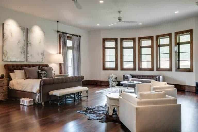 Spacious primary bedroom with hardwood flooring, white walls and a regular white ceiling. The room has a modish bed lighted by table lamps on bedside tables. There's a sitting spot in the middle along with a couch by the windows.