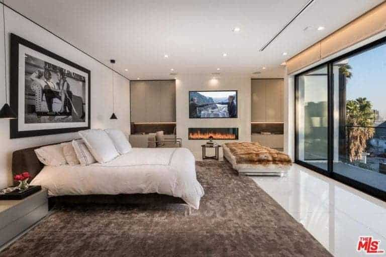Large modern primary bedroom featuring a large cozy bed, a gas fireplace and a flat-screen TV on the wall. The room also has a stylish and elegant piece of wall decor.