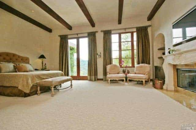 Large primary bedroom with carpeted flooring and a ceiling with exposed beams. The room offers a luxurious bed and a classy fireplace with a large TV on top of it.