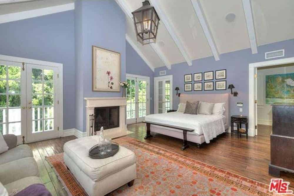 Large primary bedroom featuring blue walls and hardwood flooring, along with a tall ceiling. The room has a large comfy bed, a personal living space with a couch and a fireplace.