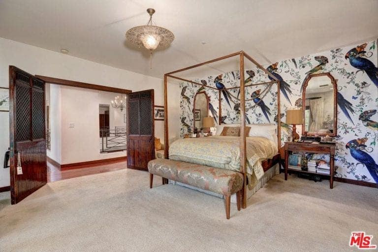 Spacious primary bedroom with a beautiful decorated wall, a classy bed set and carpeted flooring.