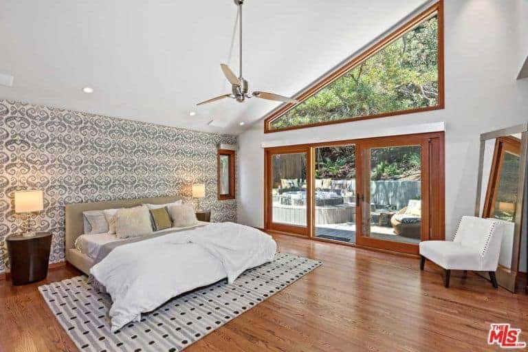 This primary bedroom boasts a tall shed white ceiling and hardwood flooring. The room has a cozy gray bed lighted by table lamps on both sides.