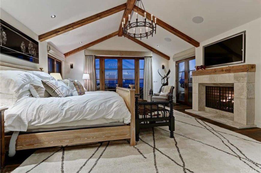 Large primary bedroom featuring a white vaulted ceiling with exposed beams along with hardwood flooring topped by a large stylish area rug. The room offers a large comfy bed and a large fireplace with a TV above it.