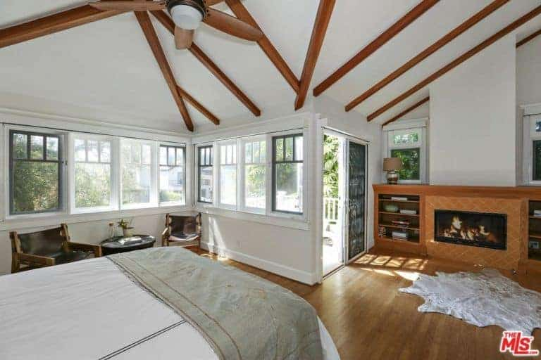 This primary bedroom is surrounded by white walls and a white ceiling with exposed beams. The room also offers a fireplace with built-in shelving on both sides.