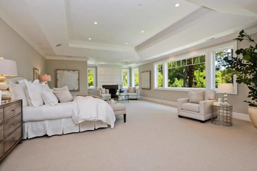 Spacious primary bedroom with gray walls, carpeted floors and a white tray ceiling. The room has a large bed and a sitting area next to the room's fireplace.