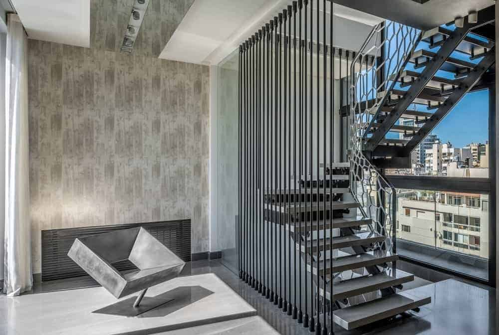 A concrete, modern seat blends in with the tiled flooring in this foyer with full height glazing and an industrial staircase on the side that's framed in black aluminum spindles and stylish glass railing.
