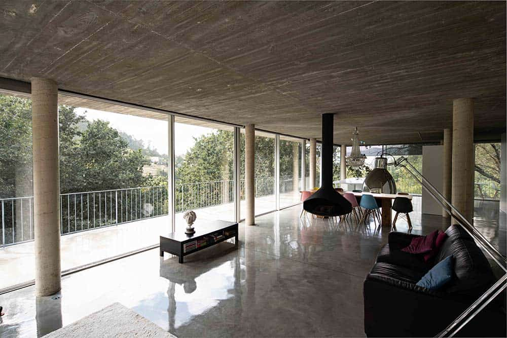 This is the living room area that has a concrete floor and ceiling contrasted by the black sofa, coffee table and the hanging black fireplace on the side. These are complemented by the glass walls.