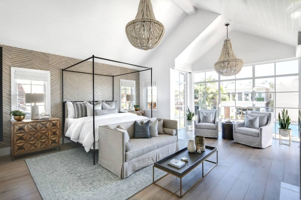 Beach style primary bedroom offers gray skirted seats and a canopy bed against the herringbone wall. It is illuminated by boho chandeliers that hung from the vaulted ceiling.