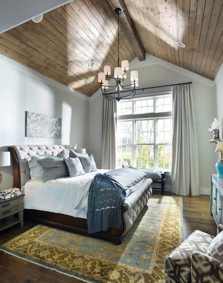 Natural light flows in through the large window in this primary bedroom with comfy seats and a gray tufted bed illuminated by a wrought iron chandelier that hung from the cathedral ceiling.