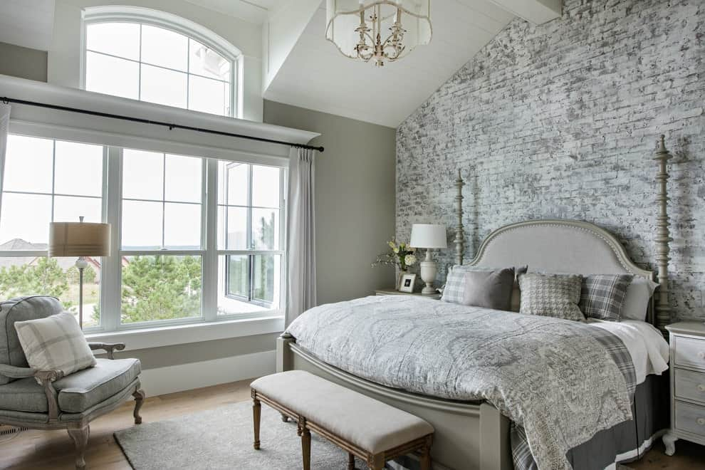 A brick accent wall sets a rustic backdrop to the upholstered bed flanked by wooden nightstands. It is accompanied by an armchair and a cushioned bench over a gray area rug.