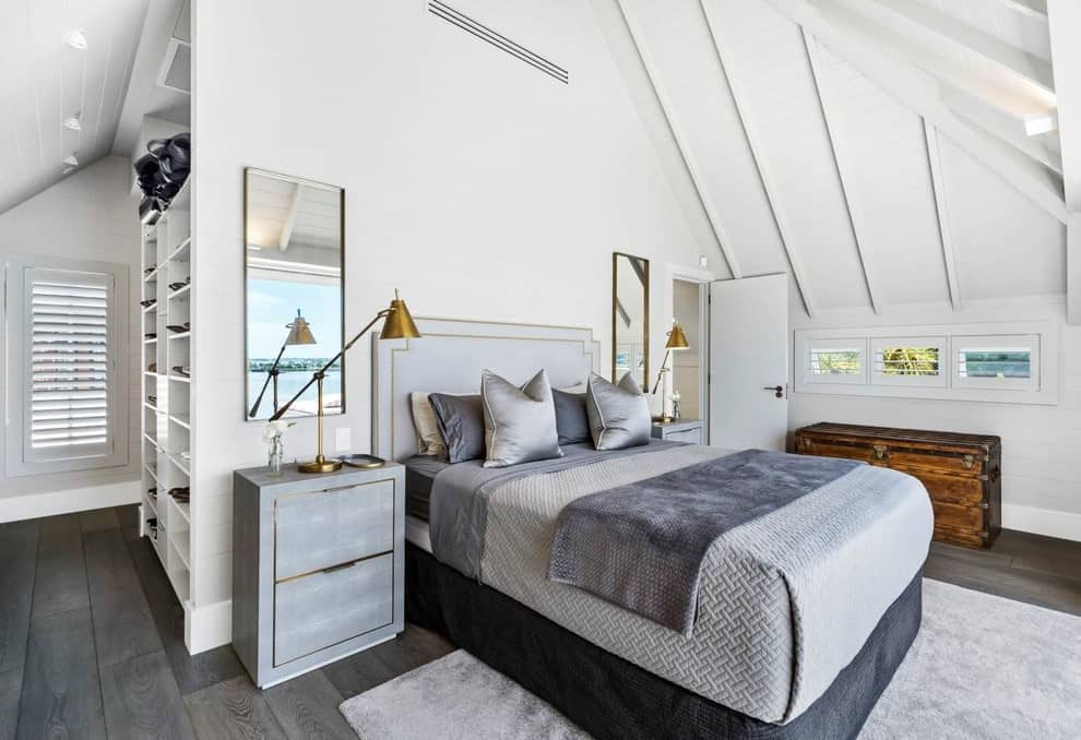 This primary bedroom offers wooden storage and a comfy bed on a gray velvet rug over wide plank flooring. It includes rectangular mirrors and light wood nightstands with gold trims complementing with the brass table lamps.