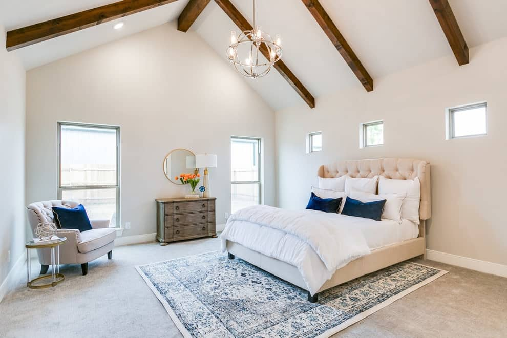 Dark wood beams stand out against the white cathedral ceiling in this primary bedroom with a wooden dresser and tufted chair matching with the beige bed over a blue shabby chic rug.