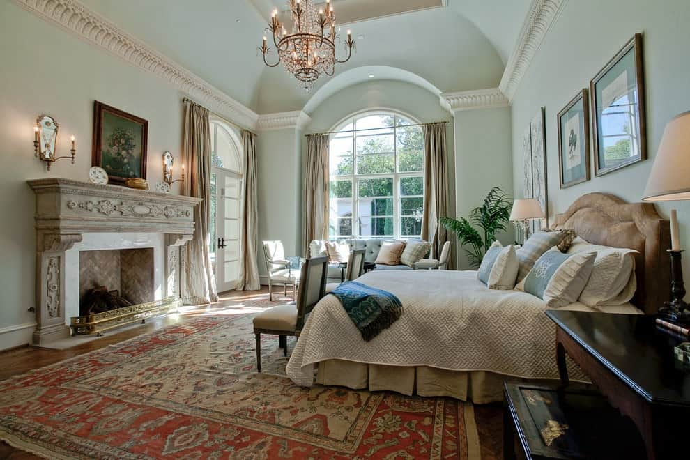Elegant primary bedroom decorated with wooden framed wall arts and a gorgeous brass chandelier that hung from the vaulted ceiling. It has cozy seats and over a red-bordered rug facing the carved fireplace lighted by wall sconces.