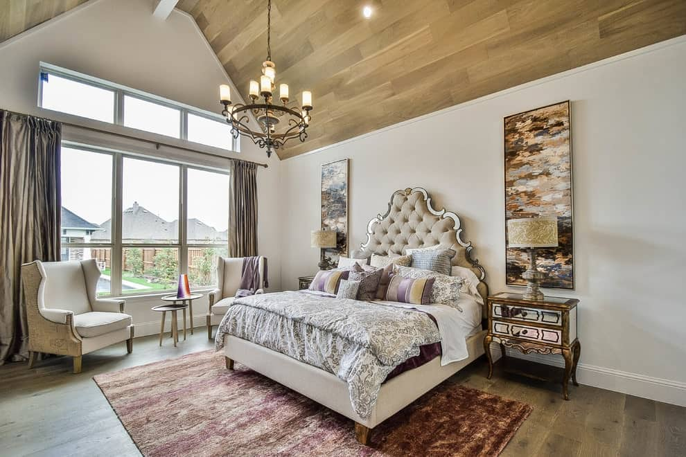 A wrought iron chandelier hangs over the gorgeous tufted bed flanked by rectangular wall arts and mirrored nightstands. There's a seating area on the side showcasing beige wingback chairs and a round modular coffee table.