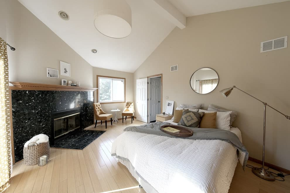 Contemporary primary bedroom boasts a comfy bed with a round mirror on top along with tufted chairs next to the black granite tiled fireplace that's framed in a wooden mantel.